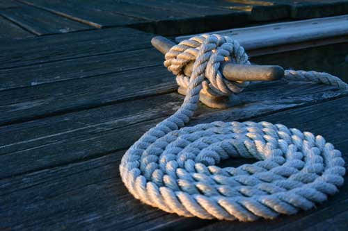 Neatly coiled boat line on a dock, coming off the cleat.